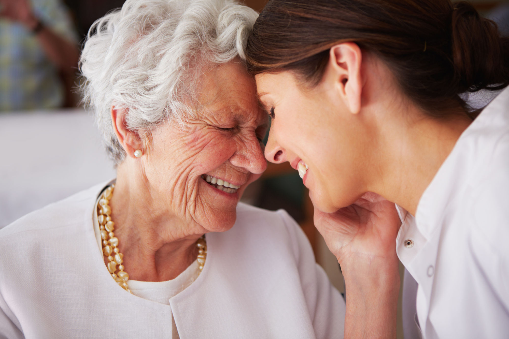 An elderly woman affectionately thanking her nurse